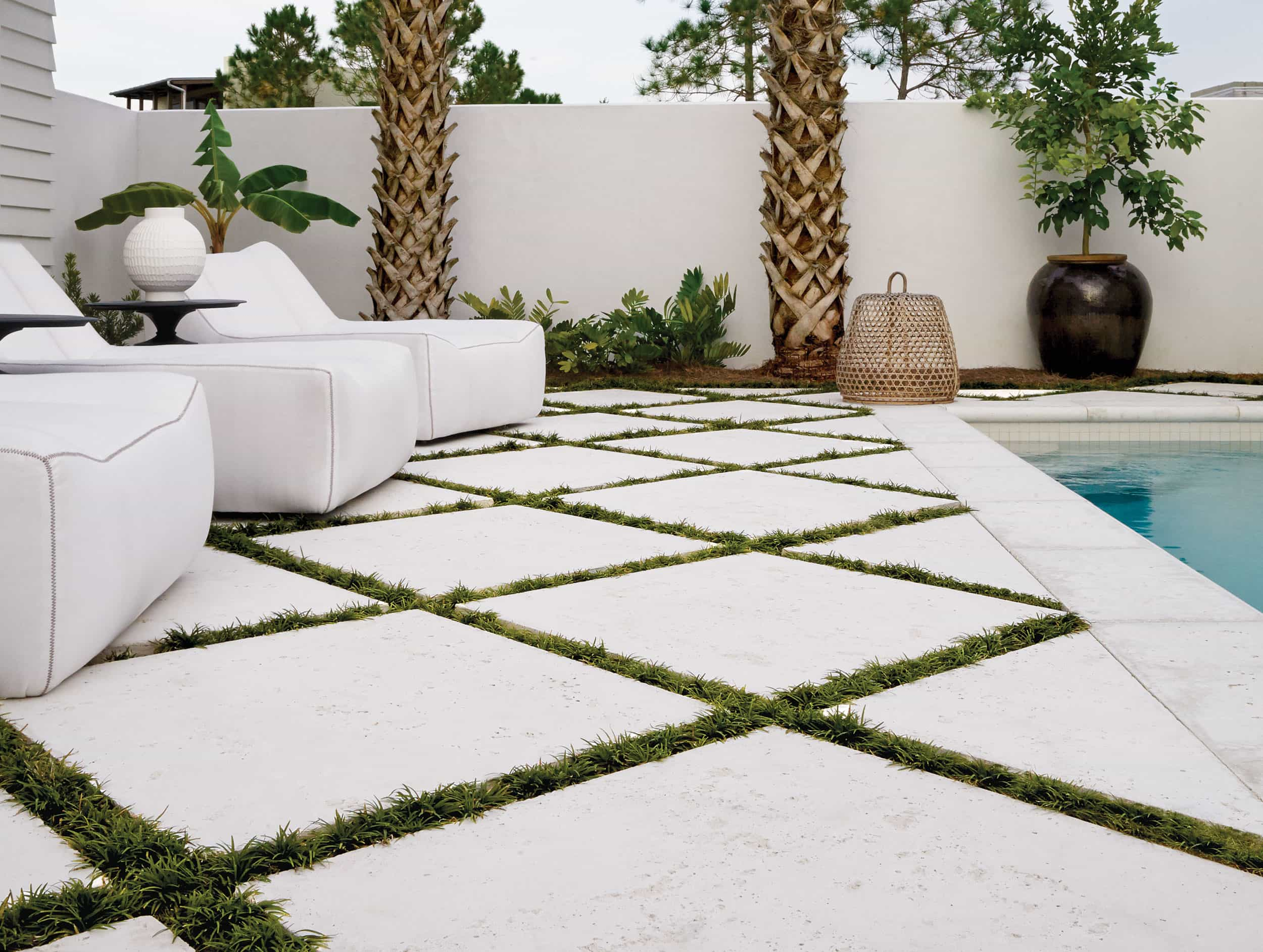 White concrete pavers with grassy joints for pool deck